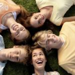 Fünf lachende Menschen, die auf dem Boden liegen und nach oben gucken