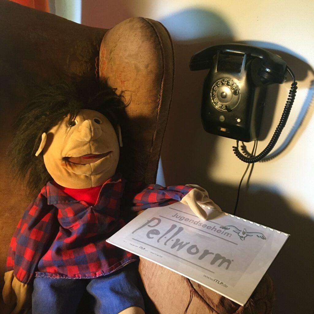 """Puppe mit Schild mit der Aufschrift """"Jugendseeheim Pellworm"""" auf Sessel neben einem Telefon"""